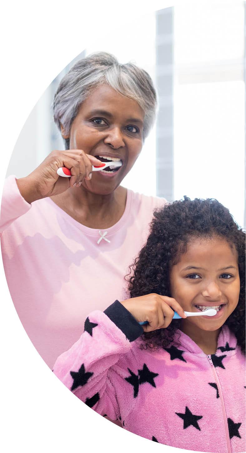 Grandmother and granddaughter brushing teeth
